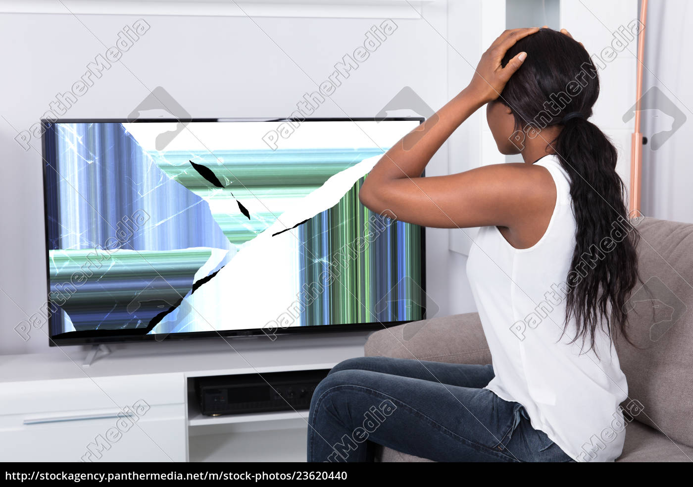 upset, woman, looking, at, broken, television - 23620440
