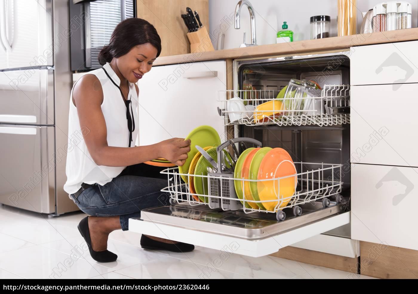 woman, arranging, plates, in, dishwasher - 23620446