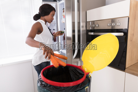 woman, throwing, carrot, in, trash, bin - 23620424