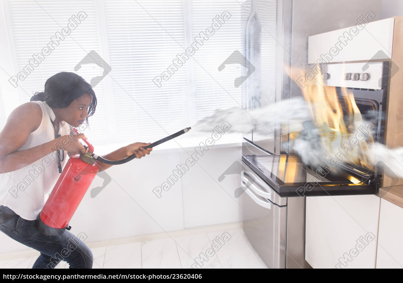 woman, using, fire, extinguisher, to, stop - 23620406
