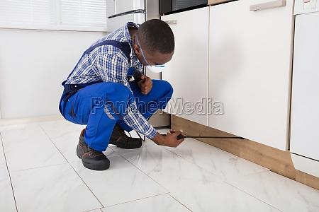 worker, kneeling, on, floor, and, spraying - 23620290