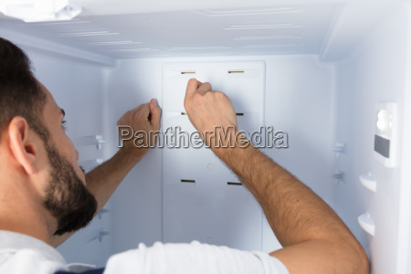 electrician, fixing, refrigerator, in, kitchen - 23624194