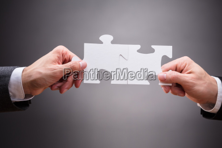 close up of businesspeople holding jigsaw