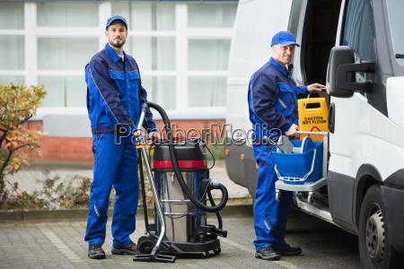 two male janitor unloading cleaning equipment