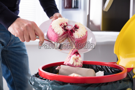 person throwing cake in trash bin