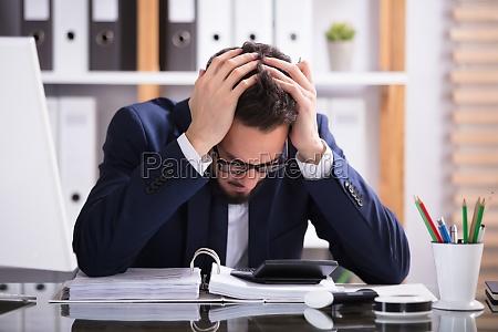 man suffering from headache working in