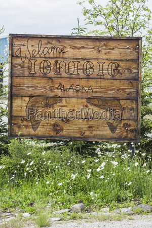 a worn wooden sign welcomes visitors