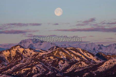 the moon rises over the mountains