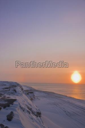 sunset through windblown snow creates a