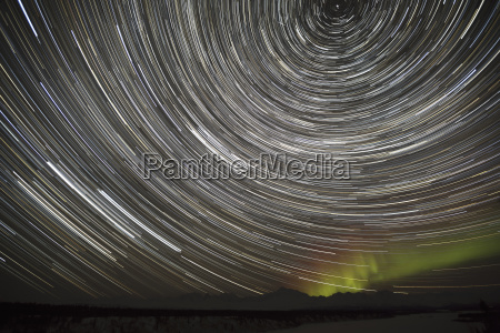 star trails and northern lights above