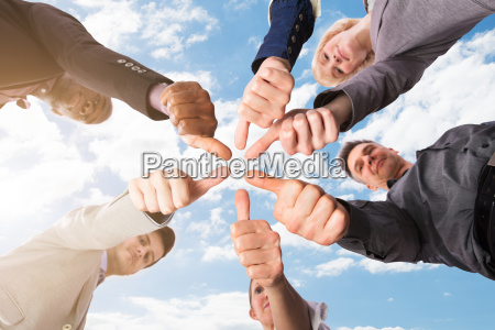 group of businesspeople gesturing thumbs up