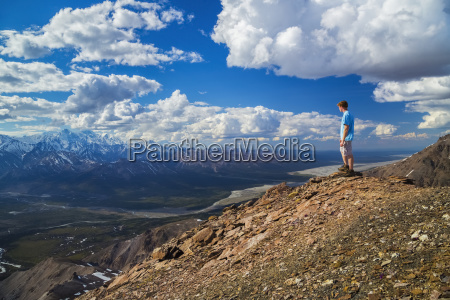 a hiker stands on a rocky