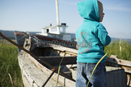 a young boy stands beside a