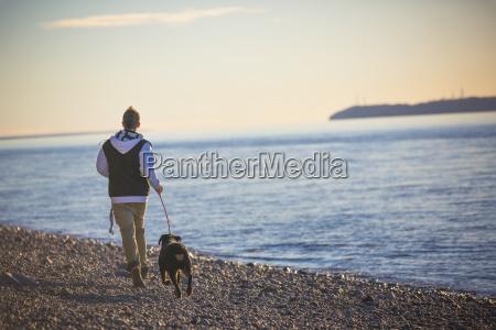 teenage boy running with his rottweiler