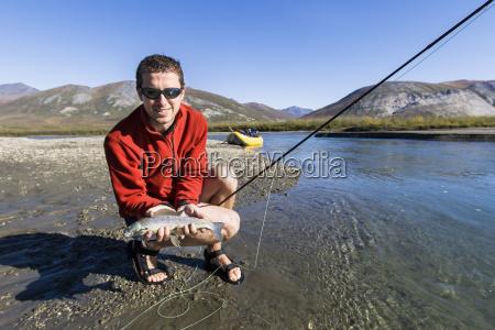 a fisherman holds a fresh grayling