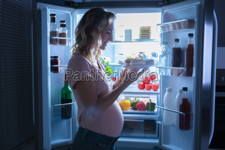pregnant woman holding plate of cookies