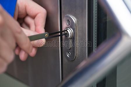 person opening door with lockpicker