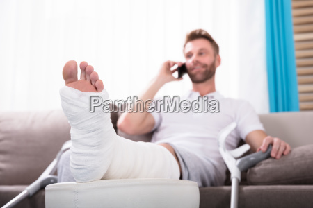 happy young man with broken leg