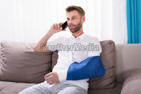 man with fractured hand talking on