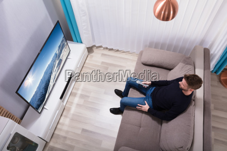 young man holding remote watching television