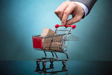 businessperson holding shopping cart with cardboard