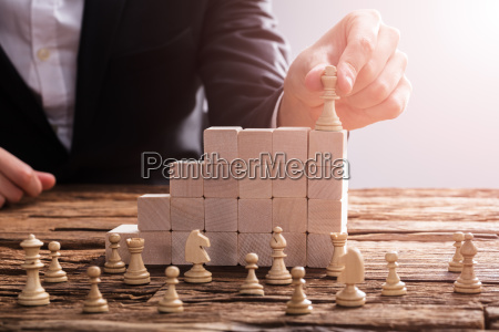 businessperson arranging chess piece on wooden
