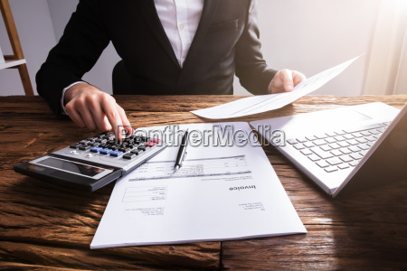 businesspersons hand calculating invoice in office