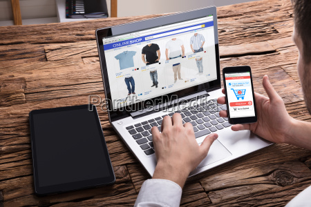 businessperson using smartphone while shopping online