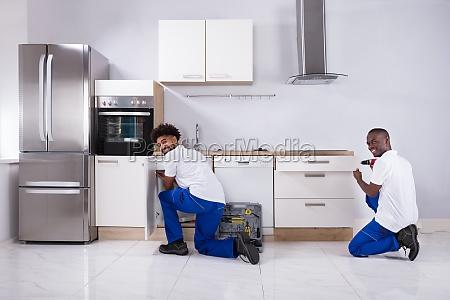 two handy men fixing the wooden