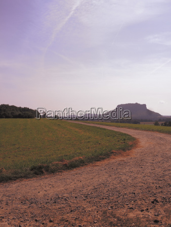 dirt road amidst grassy field against