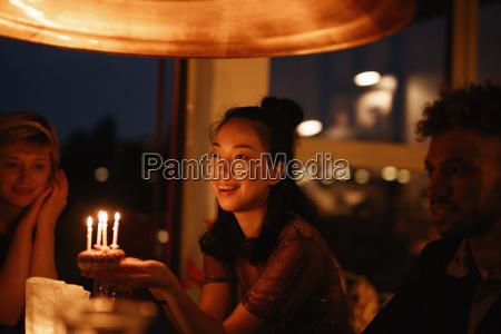 happy woman holding small birthday cake