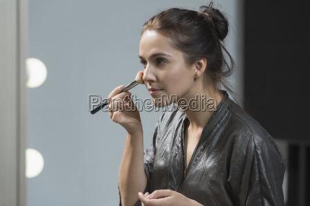 beautiful woman applying make up with
