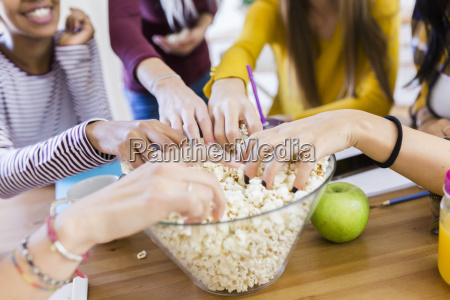 friends taking popcorn from bowl at