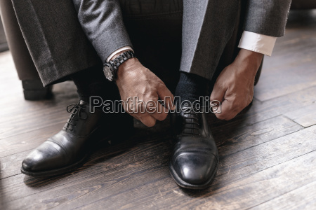 businessman putting on shoes tying shoelace