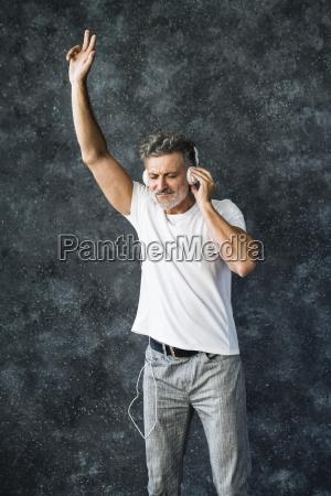 mature man having fun listening music