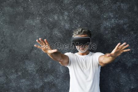 mature man wearing vr glasses reaching