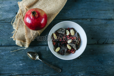 bowl with dessert of almonds pomegranate