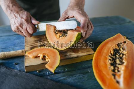 hands of senior man cutting papaya