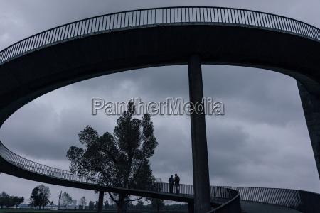 two businessmen standing on dark bridge