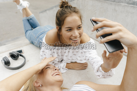 two happy young women sharing cell