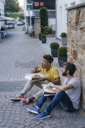 two friends eating takeaway pizza in