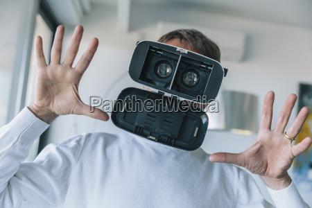 confused man wearing vr glasses making