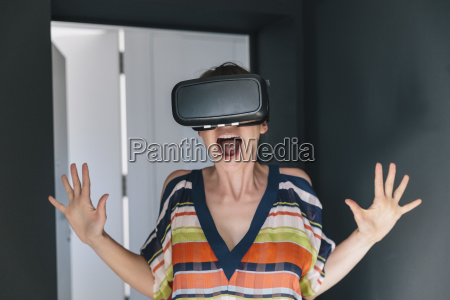 amazed woman wearing vr glasses making