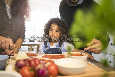 family baking pizza in kitchen daughter