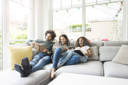 happy family sitting on couch reading
