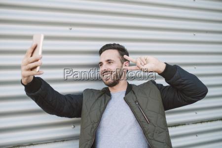 portrait of smiling man taking selfie