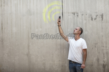 man holding up phone looking for
