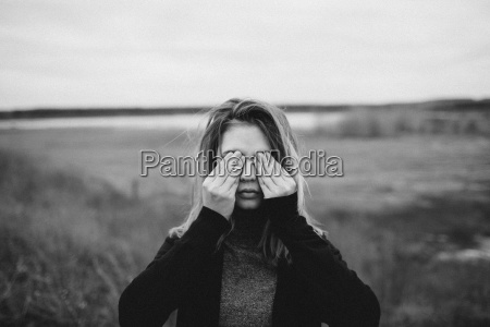 teenage girl covering eyes while standing