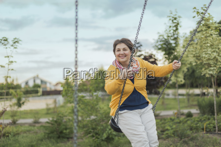 smiling woman playing on swing at