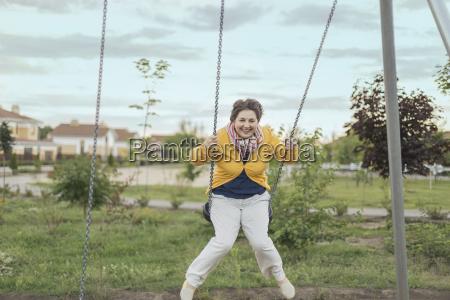 happy senior woman swinging on swing